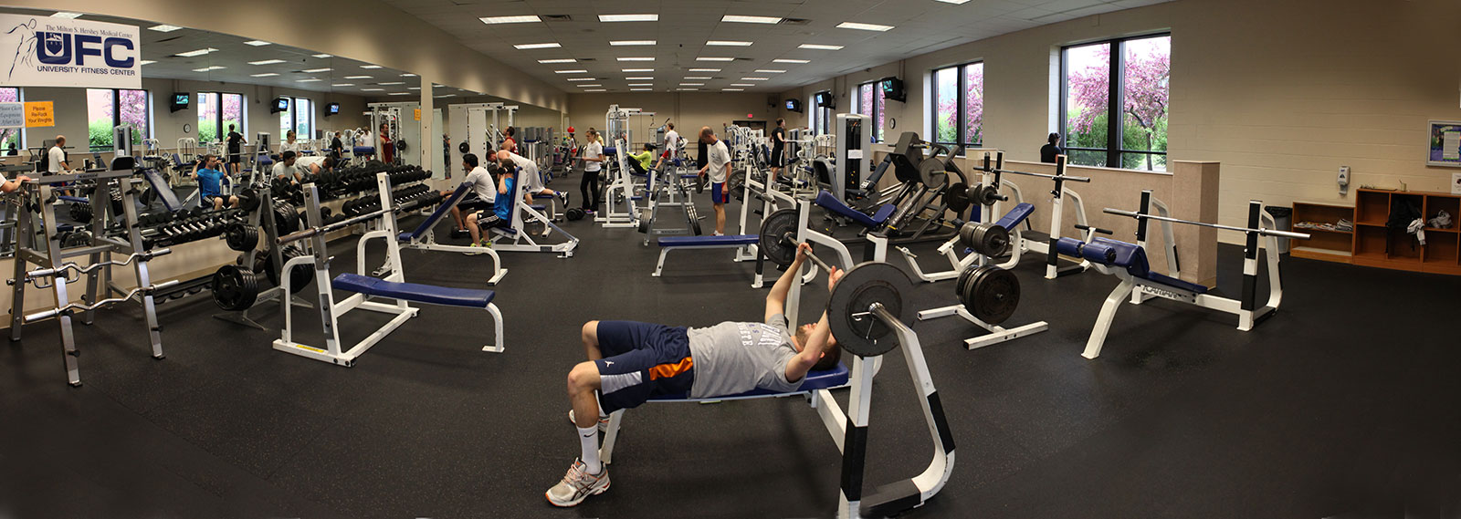 Penn State College of Medicine's University Fitness Center is seen in a 2013 panoramic photo. Various equipment and weight benches can be seen in rows, with mirrors along one wall. People are using some of the equipment.