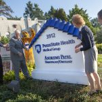 Four people stand around an outdoor sign that reads: Penn State Health Medical Group Andrews Patel Hematology/Oncology
