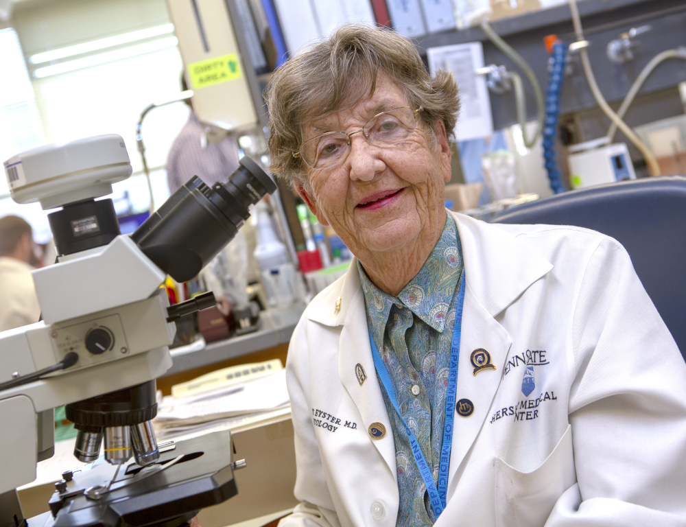 Dr. Elaine Eyster poses for a photograph in a lab, wearing a lab coat. A microscope is nearby.