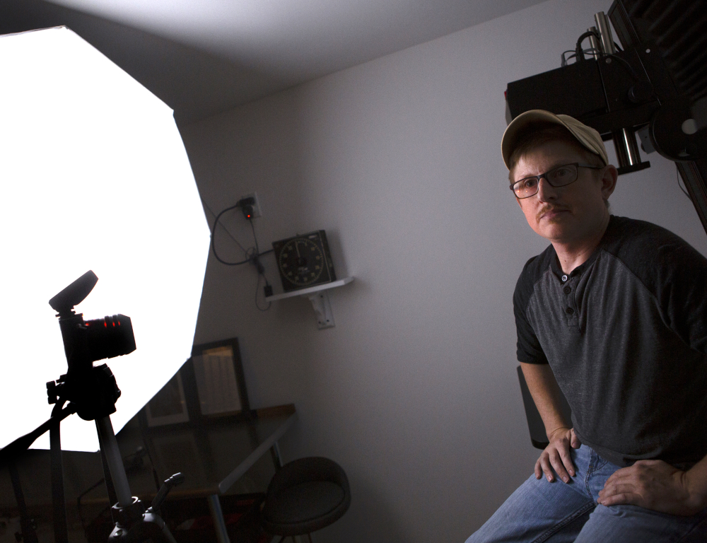 A man wearing a ballcap, shirt and jeans sits on a stool in a photo studio. A camera and light panel are on the left side of the photo.