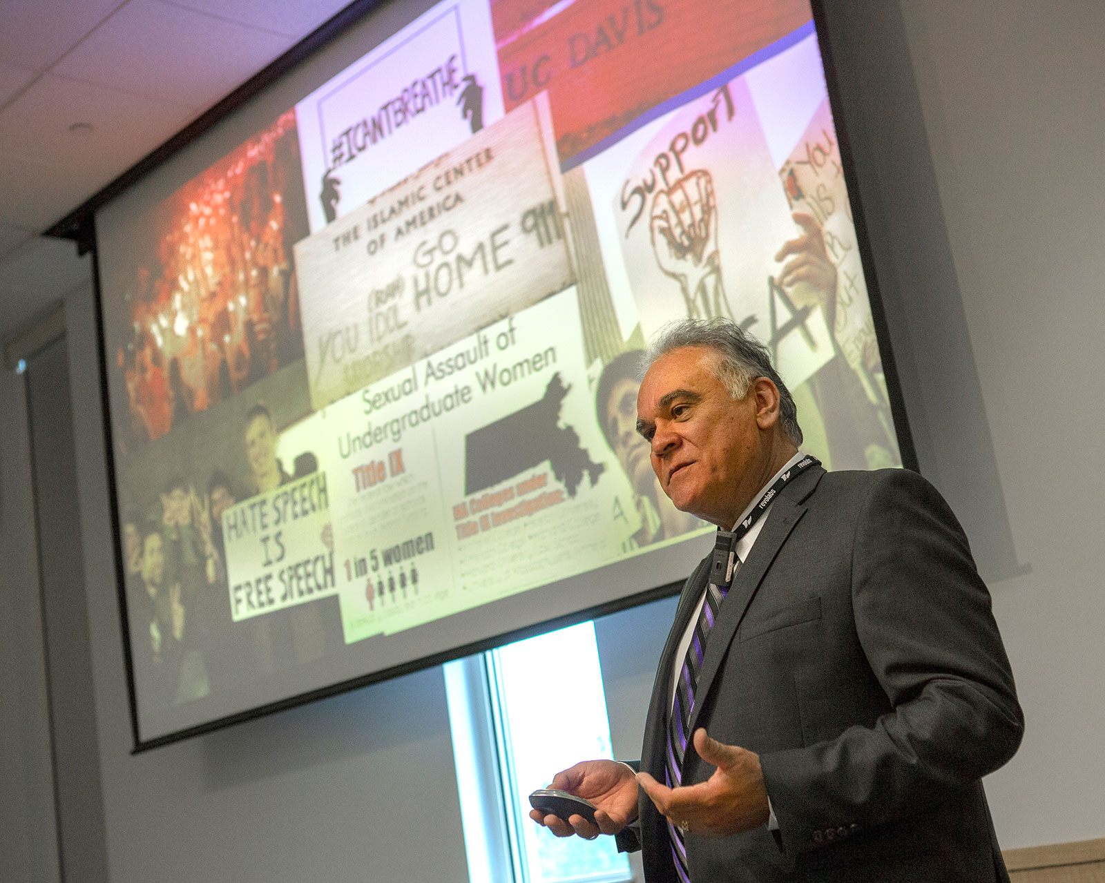 David Acosta, chief diversity officer with the AAMC, is pictured speaking at an event in August 2018 at Penn State College of Medicine in Hershey, PA. Acosta is seen in the foreground with a large presentation screen behind him depicting images related to bias.