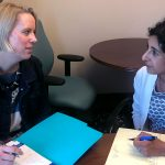 Dr. Jennifer Kraschnewski and Dr. Deepa Sekhar are pictured sitting at a table with folders open in front of them.
