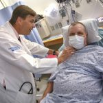 A physician in a white coat stands next to a patient who's in a hospital bed. The doctor's hands are placed on the patient's shoulder and neck area.