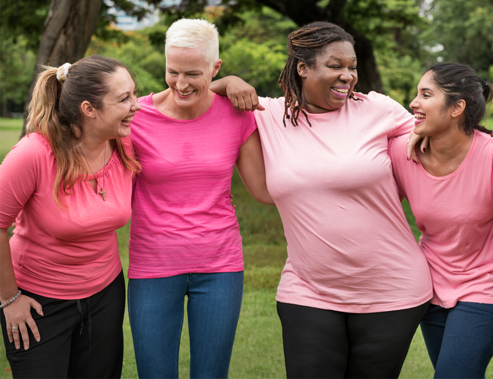 Four women wearing pink t-shirts stand with arms around each other, smiling. Grass and trees are in the background.