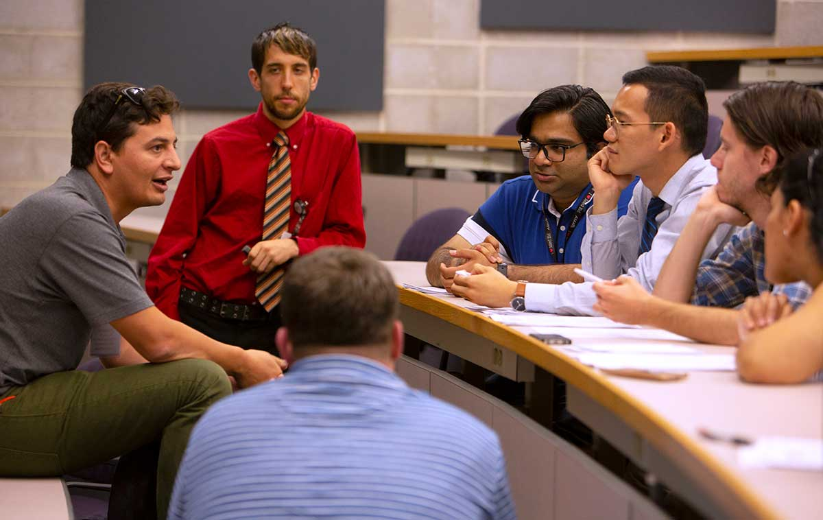 "Six medical students sit at a conference room table and listen to a man talk at the American Medical Association's ""Accelerating Change in Medical Education"" conference. Behind him Dr. Joshua Davis of Penn College of Medicine, stands and listens."