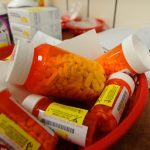 Bottles of prescription pills sit in a basket on a counter. Behind them are other medicine and a book.