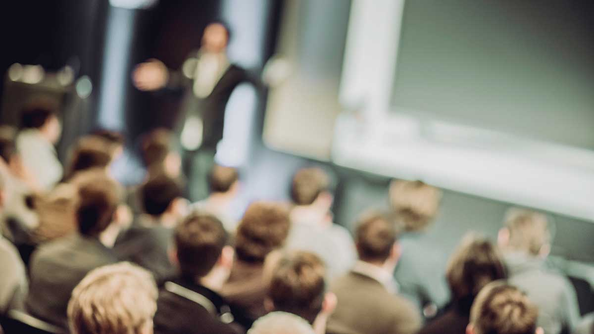 Out of focus image of man standing on a stage and speaking in front of a large audience. Backs of the audience members heads are visible. They are seated in chairs.