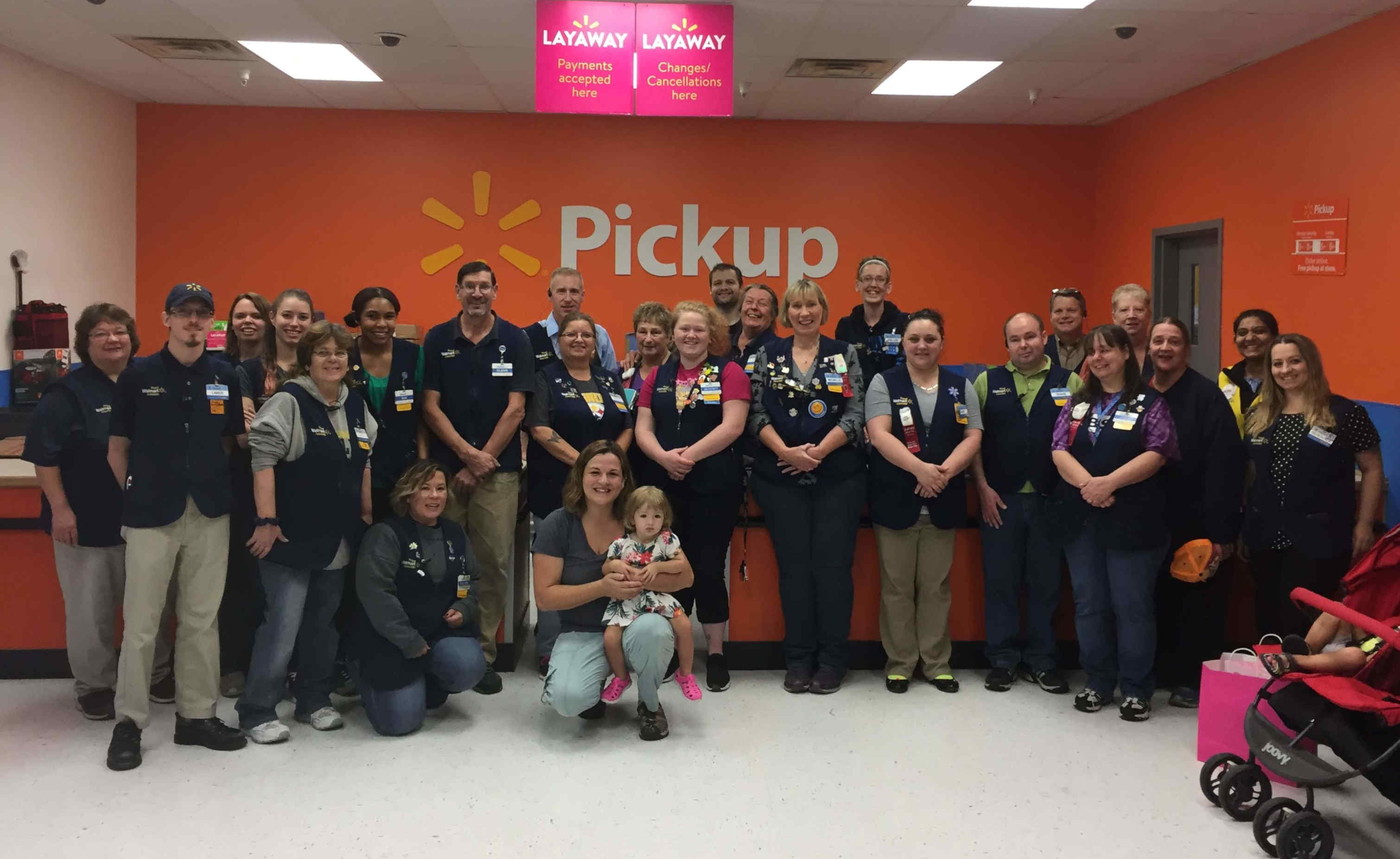 A group of people in Wal-Mart vests pose for a photo with a woman and her young daughter.