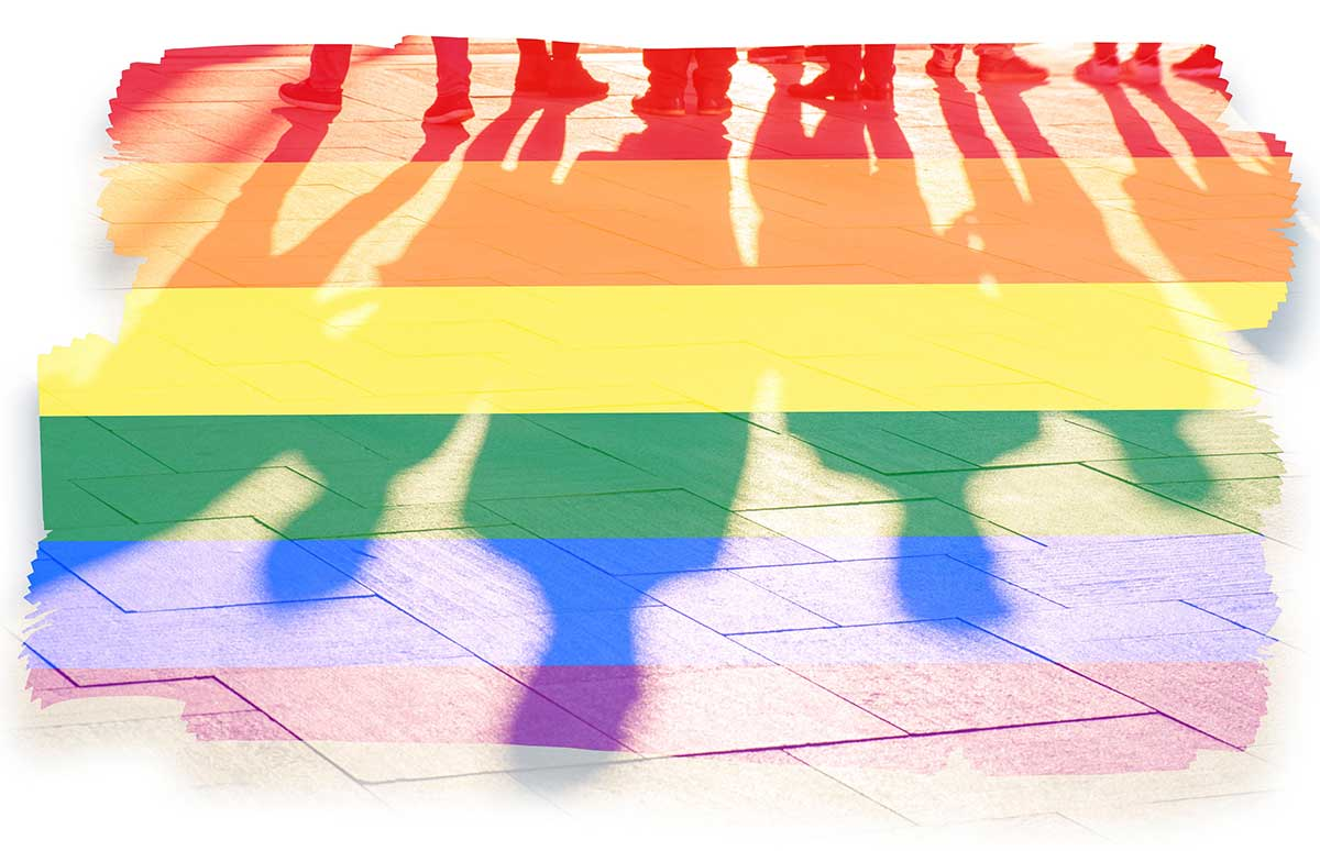 Shadows of people in rainbow colors stand on a sidewalk. Over them are rainbow stripes.