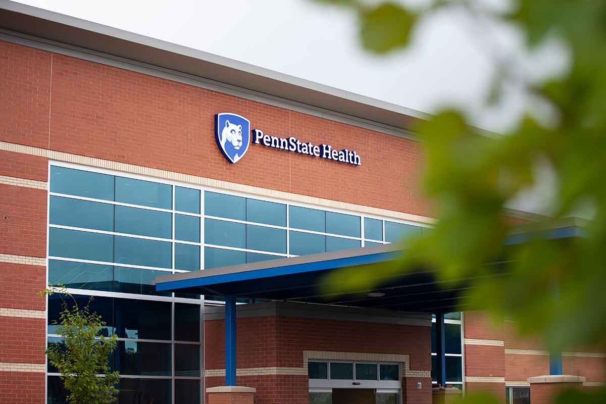 The front entrance of the new Penn State Health Medical Group - Lime Spring Outpatient Center shows a red brick building with the Penn State Health logo, large windows, an entrance roof and tree branches in the foreground.