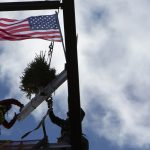 Two construction workers work to secure a white beam, onto which an evergreen tree and American flag are mounted, atop a building.