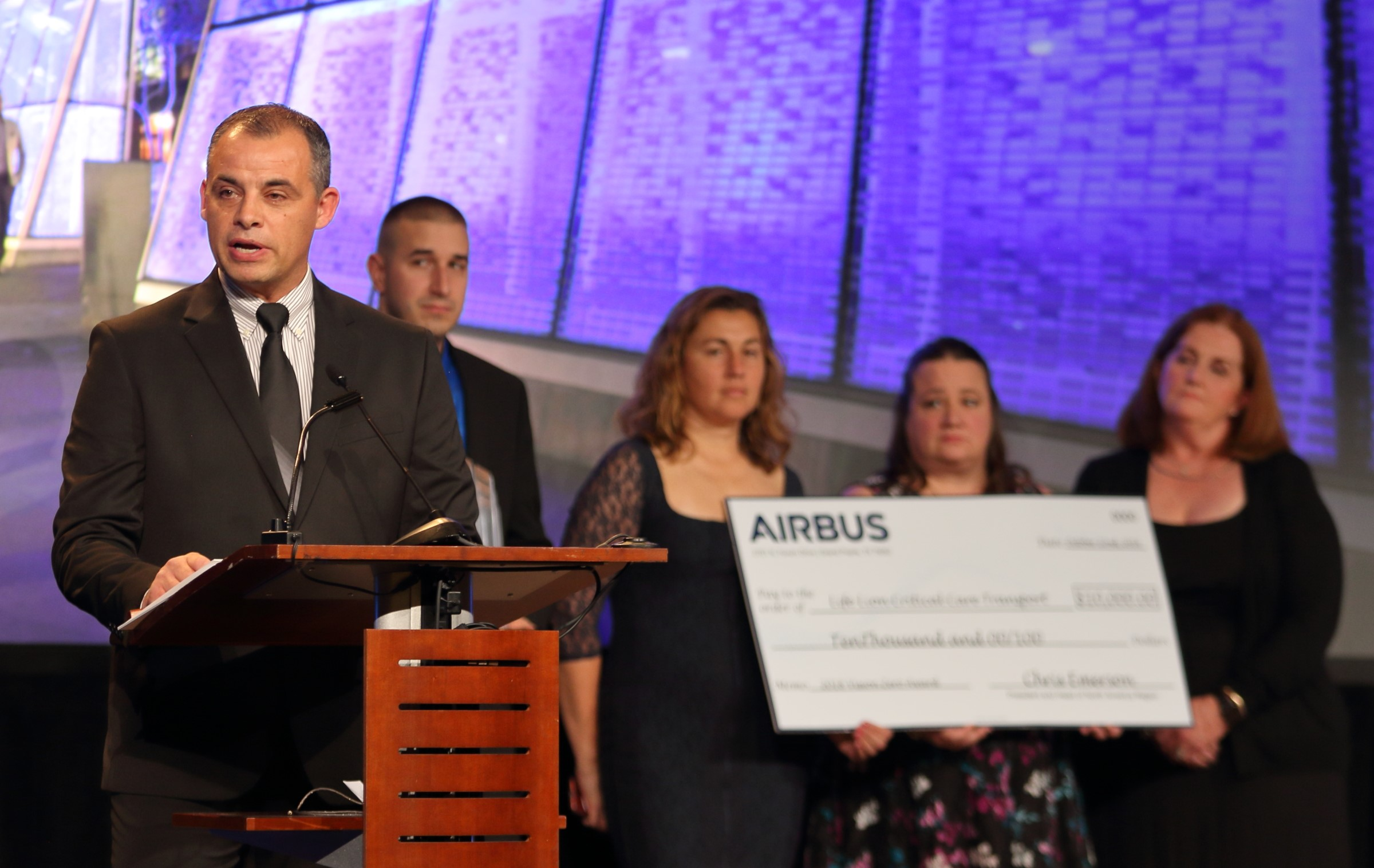 A man in a suit stands at a lectern speaking. Four people stand behind him holding an oversized cardboard check.