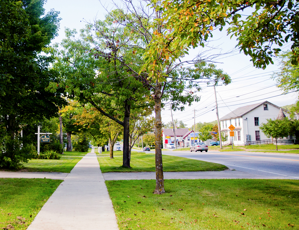 The view down a long sidewalk of a residential neighborhood. A grassy area lined with trees is between the sidewalk and the road. Some cars and buildings are in the background.