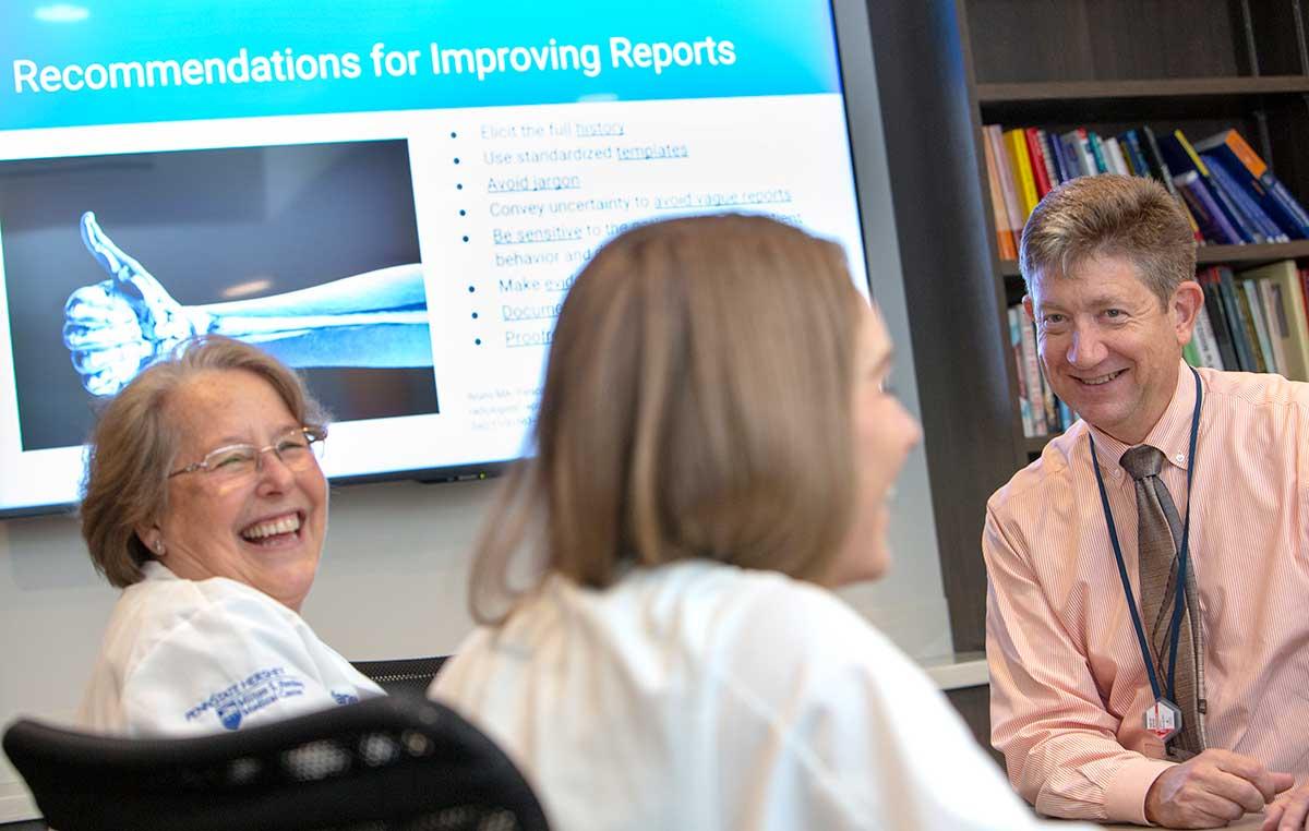 "Dr. Timothy Mosher, chair of the Department of Radiology at Penn State College of Medicine, smiles. Two women wearing white lab coats with the Milton S. Hershey Medical logo on them, smile. Behind them is a PowerPoint slide that says ""Recommendations for Improving Reports"" and has an image of an arm with a thumb up. Behind Dr. Mosher is a bookshelf with books."