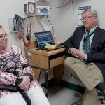 Denise Brown, who suffers from aortic stenosis and needed heart valve replacement surgery, sits with Dr. John Conte at Penn State Milton S. Hershey Medical Center. Brown is sitting in an exam room on a chair next to Conte, who is sitting on a stool next to a desk on which his laptop sits, open. Brown wears a cannula in her nose to assist with breathing.