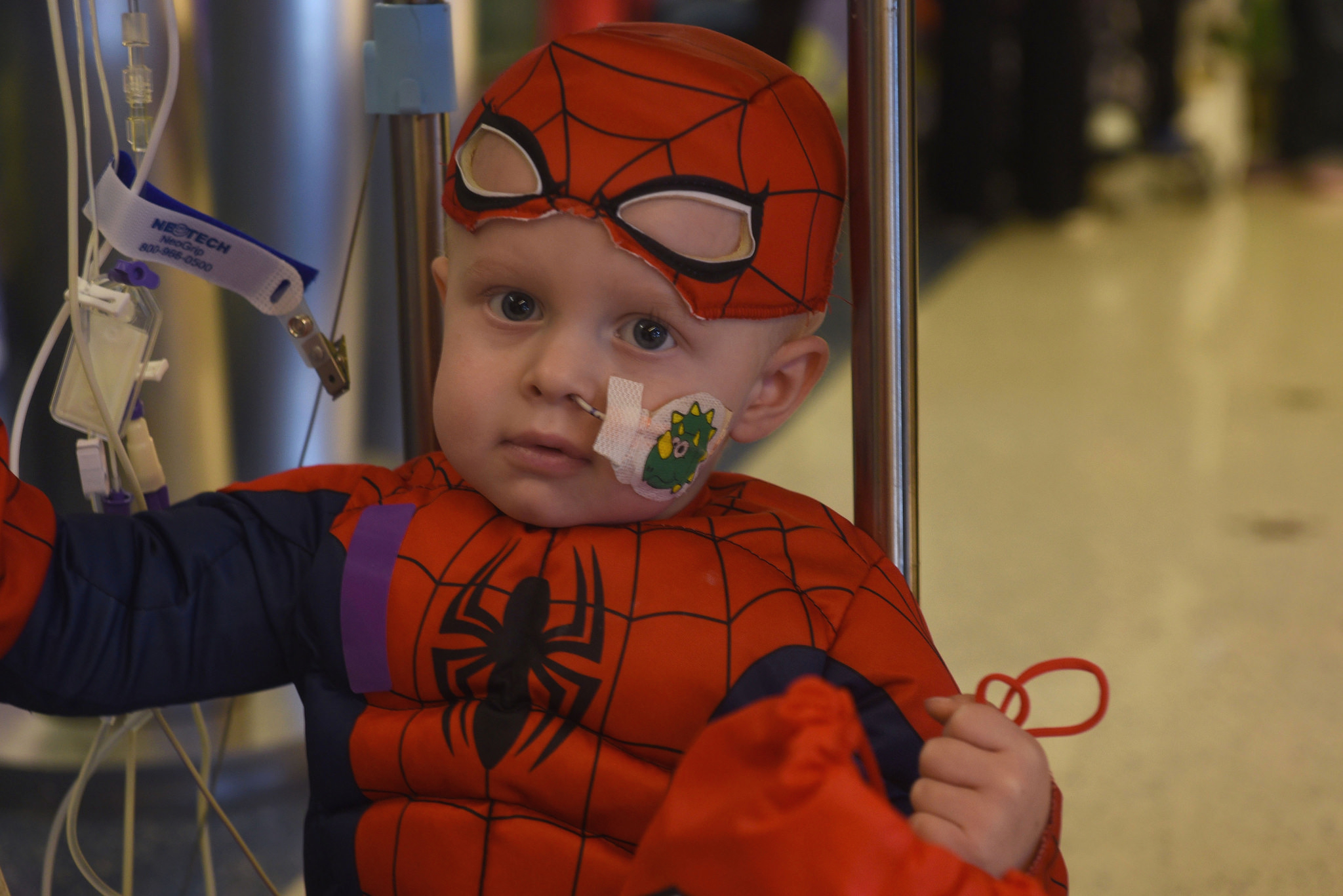 A young child in a Spiderman costume poses for a photo while sitting on the base of an IV pole. Some IV cords are in the background. The child holds a red bag with one hand.