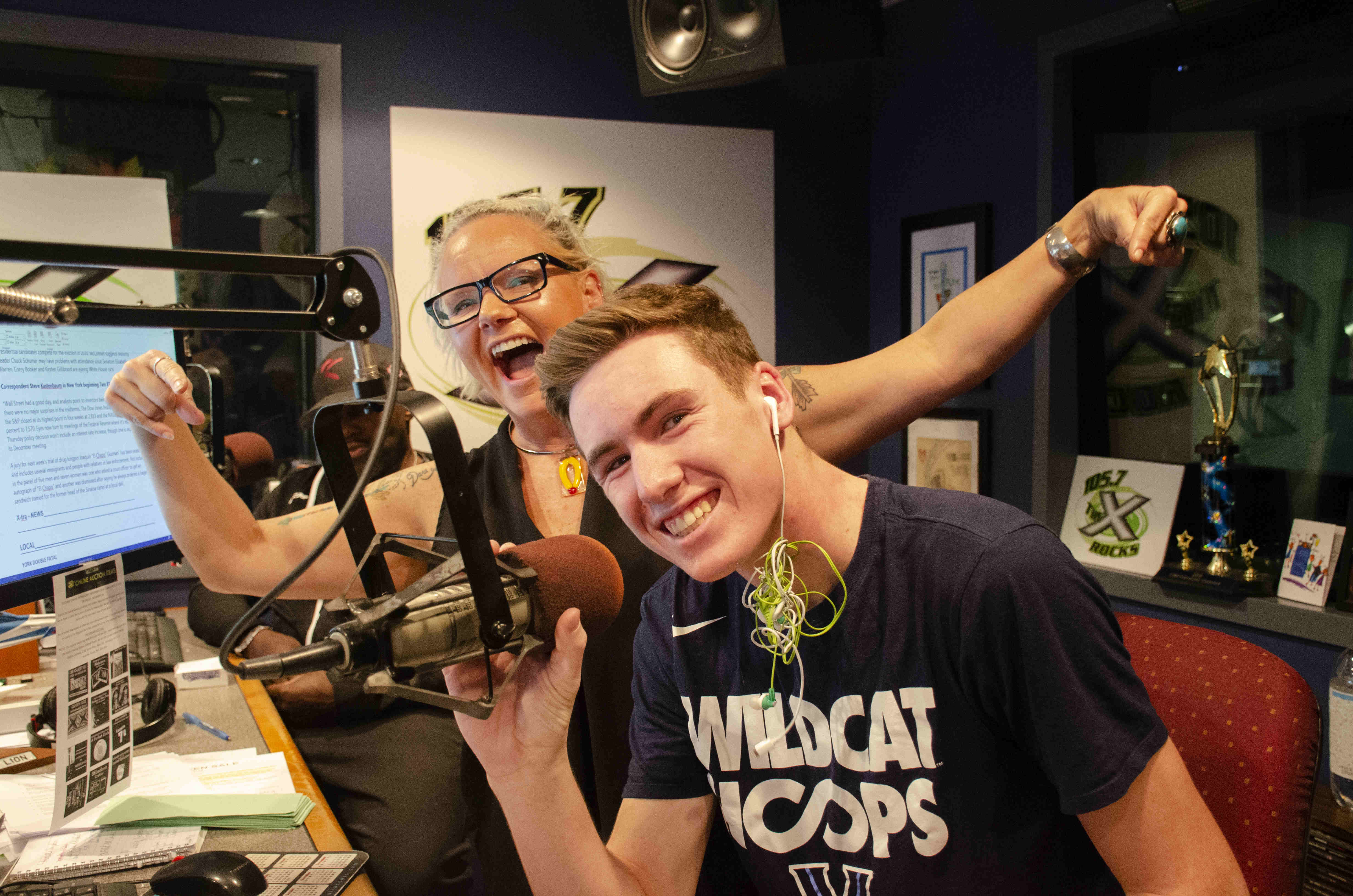 A teenage boy sits at a microphone in a radio studio, smiling. A woman stands behind him with arms outstretched, also smiling.