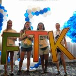"Four teenage girls hold oversized letters that spell out ""FTK."" Blue and white balloons and a window are in the background."