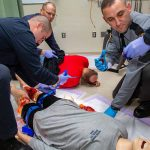 Three Pennsylvania State Police cadets learn how to apply a tourniquet during Stop the Bleed training. A man in the front-left tightens a tourniquet strap on a dummy, which has a fake gunshot wound on its right leg and blood on its left leg. A man in the back-left holds a cloth to the back of an actor. A man in the front-left reaches for a device with his gloved hand, which is covered in fake blood. The arm of another cadet reaches in holding a device. They are working in a clinical room with a vinyl floor and a curtain on the left.