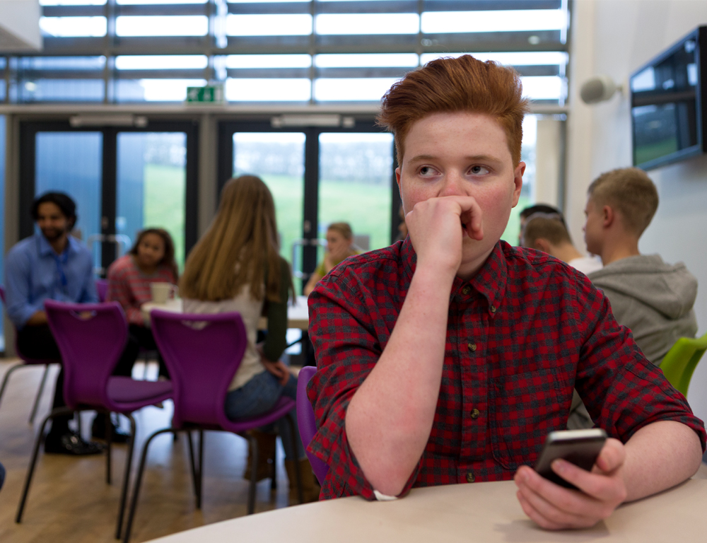 A teenage boy sits at a table in a school cafeteria. Other children are seated at other tables in the background.