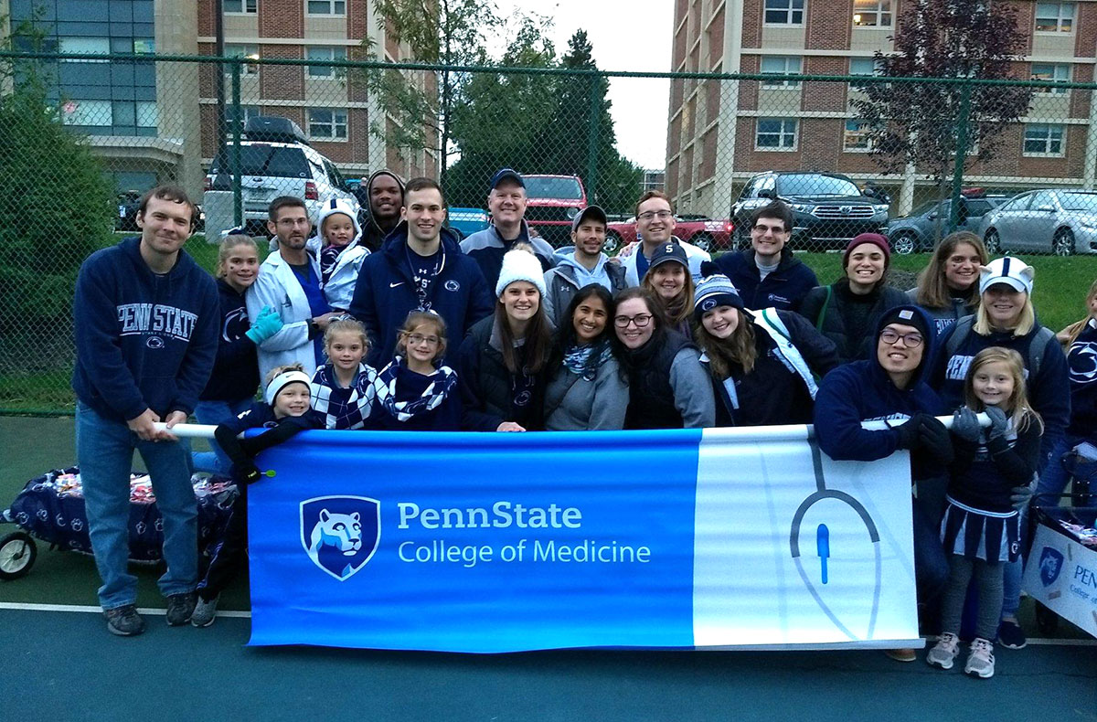 A group photo shows faculty, staff, students and family members holding a banner that says Penn State College of Medicine.