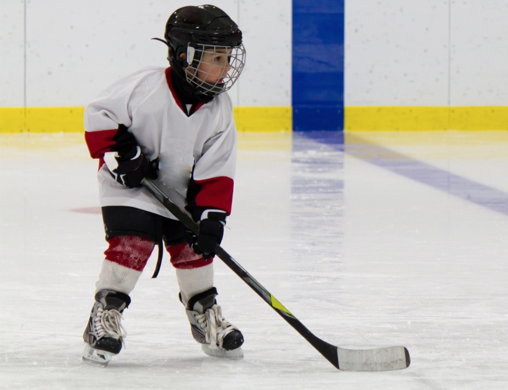 A young child in hockey gear holds a hockey stick and skates on the ice.