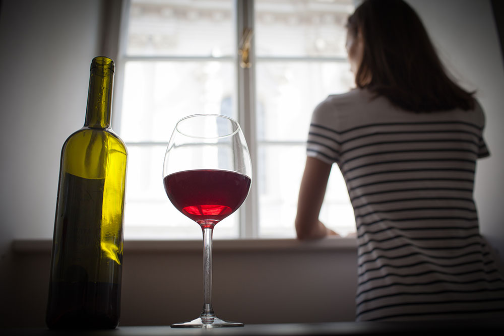 A woman stares out a window. Behind her, in the foreground, a glass of wine sits next to a bottle.