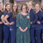 Nine women employees of the Heart and Vascular Progressive Care Unit at Hershey Medical Center pose in the middle of the unit's hallway. Julie Werner, nurse manager, stands in the middle of the group wearing a dress and ID badge. The other women stand on either side of her angled to the side with their hands on their hips smiling.