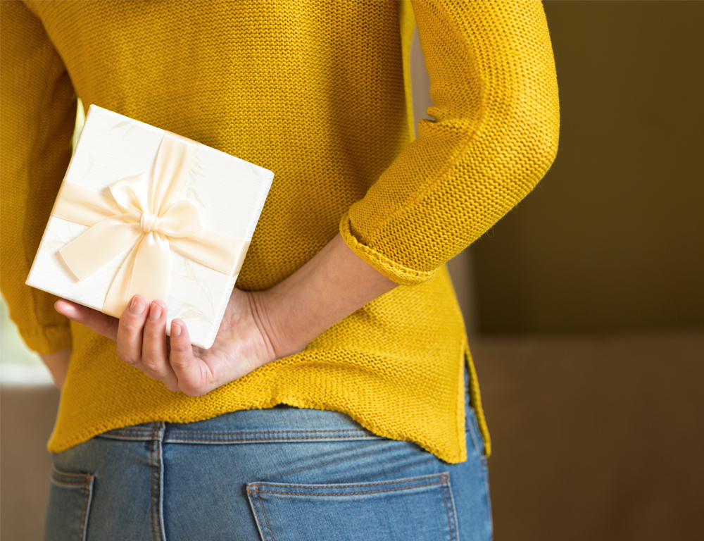 A woman in a sweater and jeans is standing, holding a small, wrapped gift behind her back with her right hand.