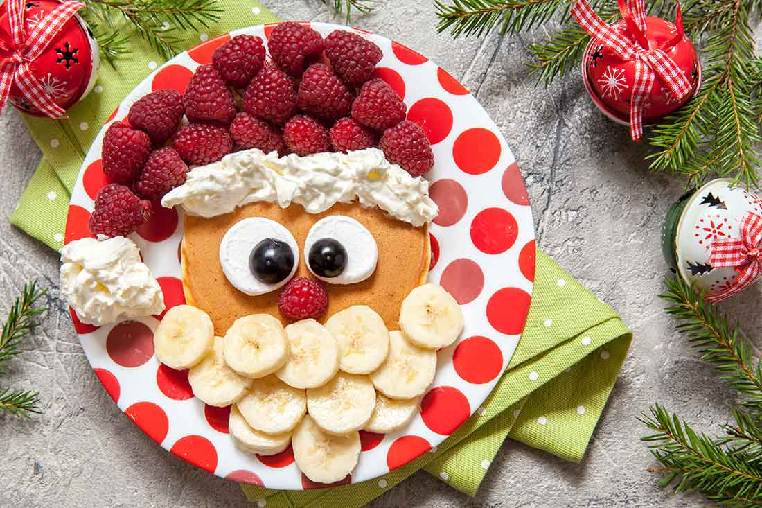 A plate surrounded by evergreens and holiday decorations features raspberries, bananas, whipped cream, blueberries and marshmallows arranged to look like the face of Santa Claus.