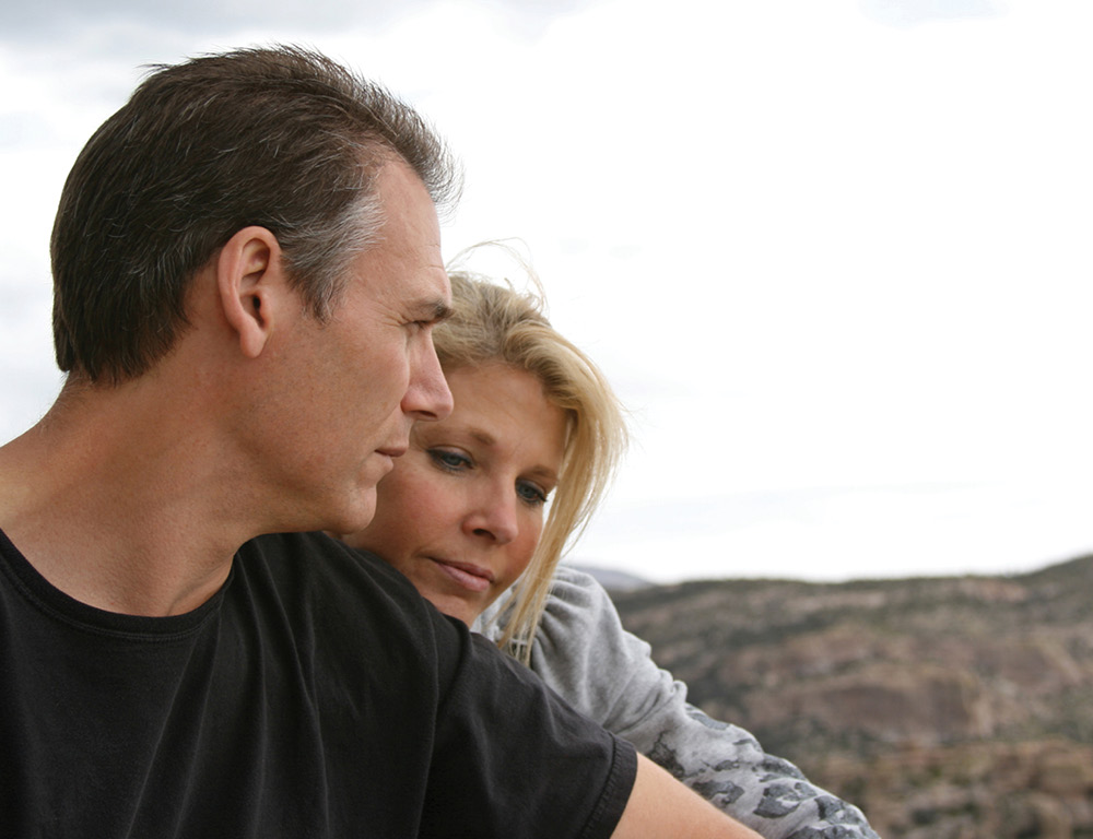 A man facing the camera looks over his left shoulder. A woman has her head resting on the upper part of his left arm. A hill is in the background, out of focus.