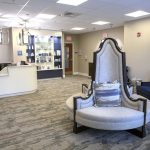 The waiting room at Esteem Penn State Health Cosmetic Associates features plush chairs, a shelf containing products behind a receptionist desk, with the Esteem logo on the wall behind it. A flat screen TV is attached to a nearby wall.
