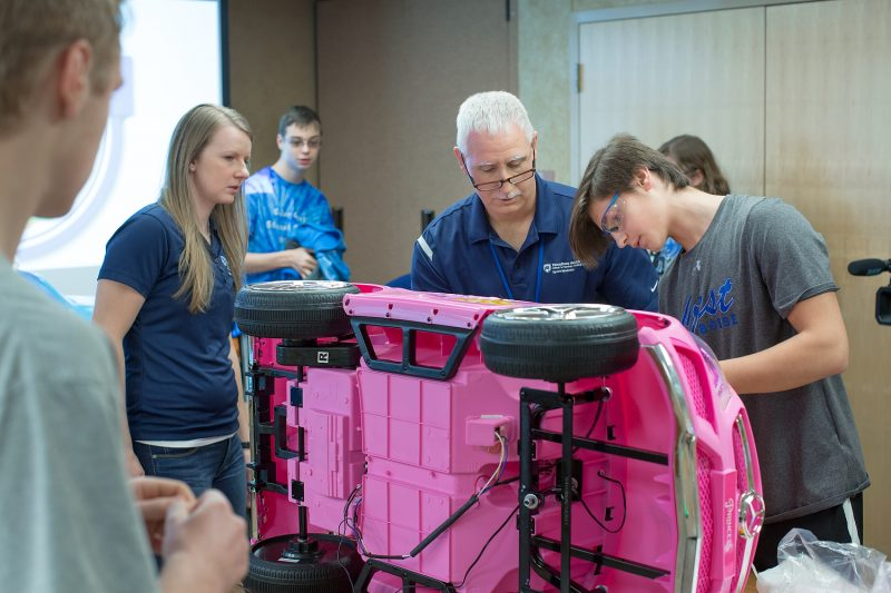 Three people work on a pink toy car, which is turned on its side and propped up on a table. Three other people stand nearby, looking on.
