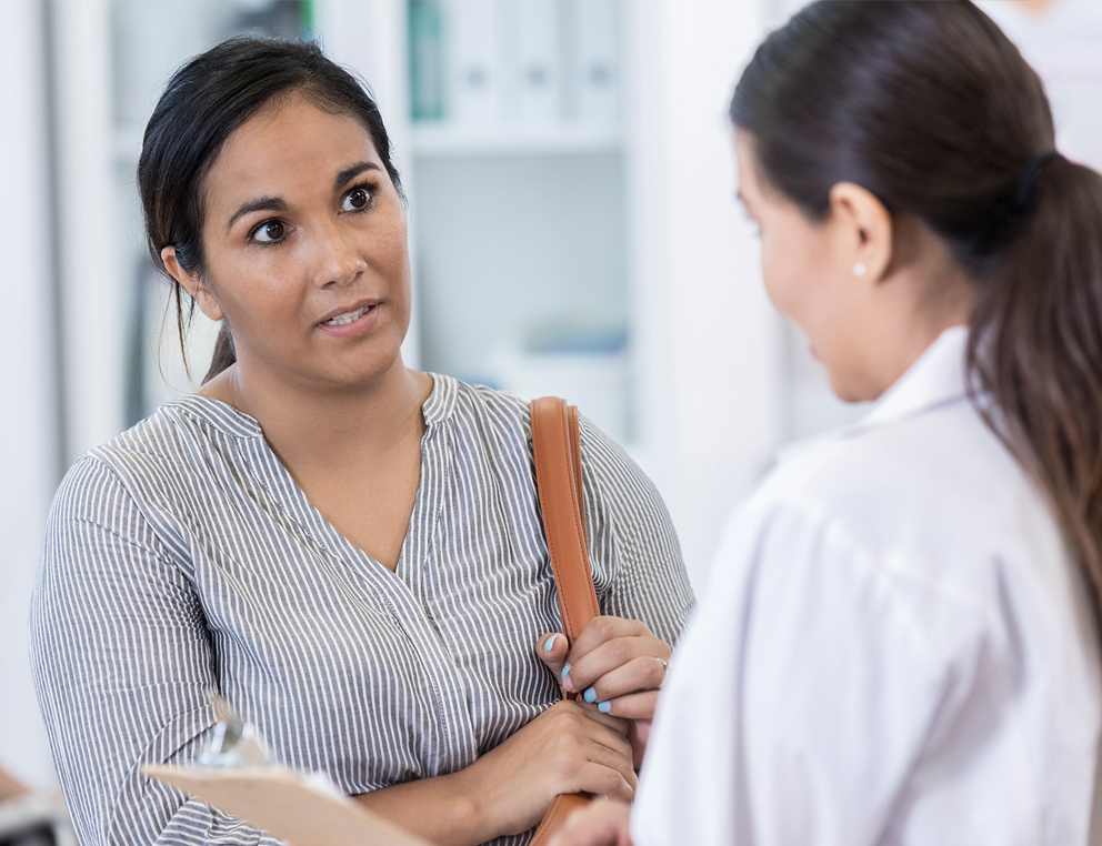 A woman in a striped shirt with a purse over her left shoulder speaks with a female doctor in a physician's coat.