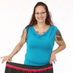 Katie Rodriguez smiles as she holds the large sweatpants she used to wear before her bariatric surgery in front of her waist. She is wearing a sleeveless top and has tattoos on her arms and chest. She has long hair and glasses.