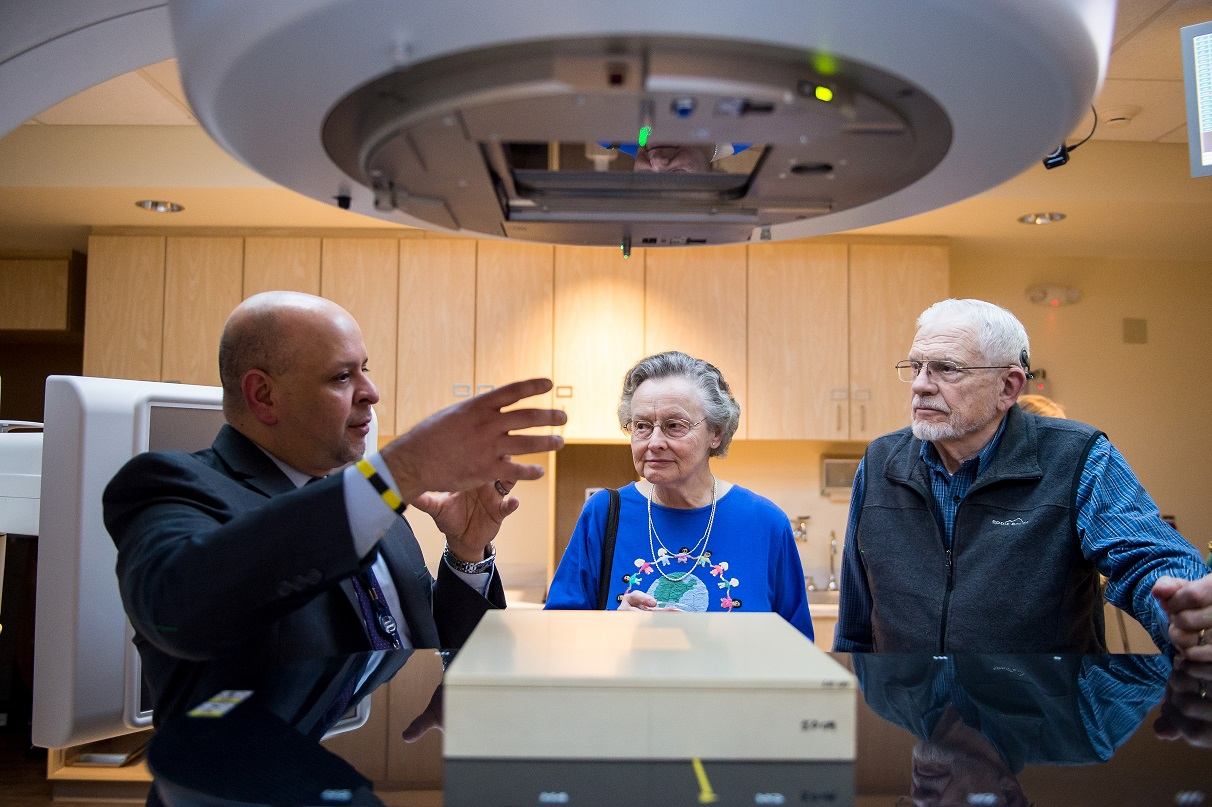 Three people talk next to a. large medical machine