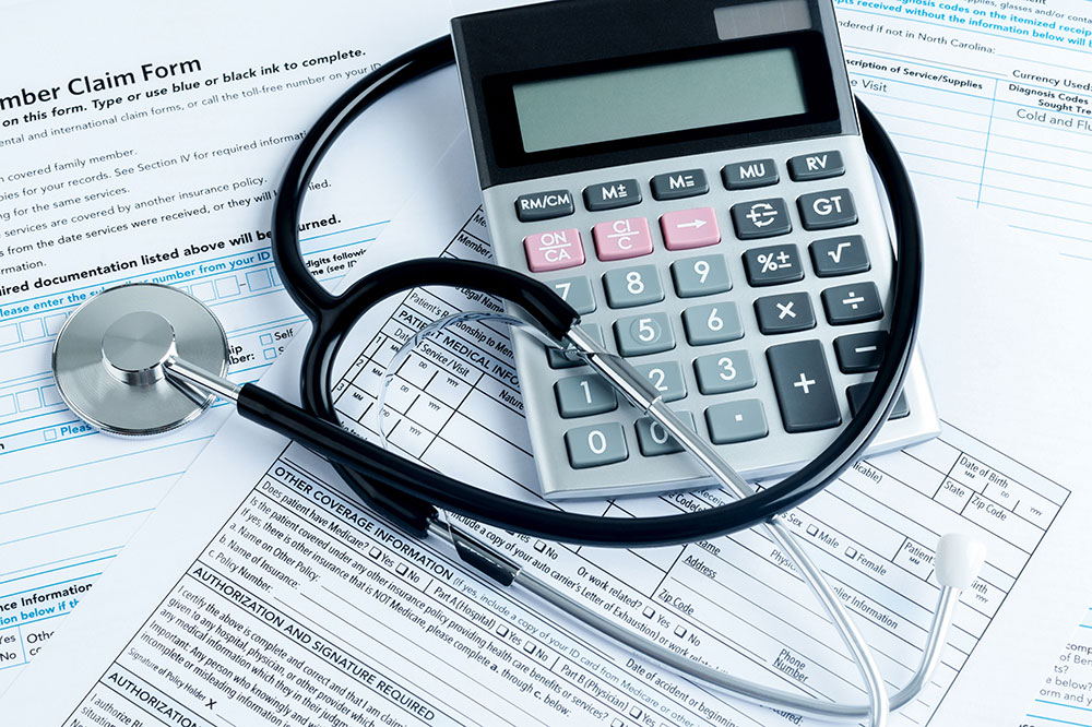 A stethoscope is wrapped around a calculator atop a pile of medical insurance forms.