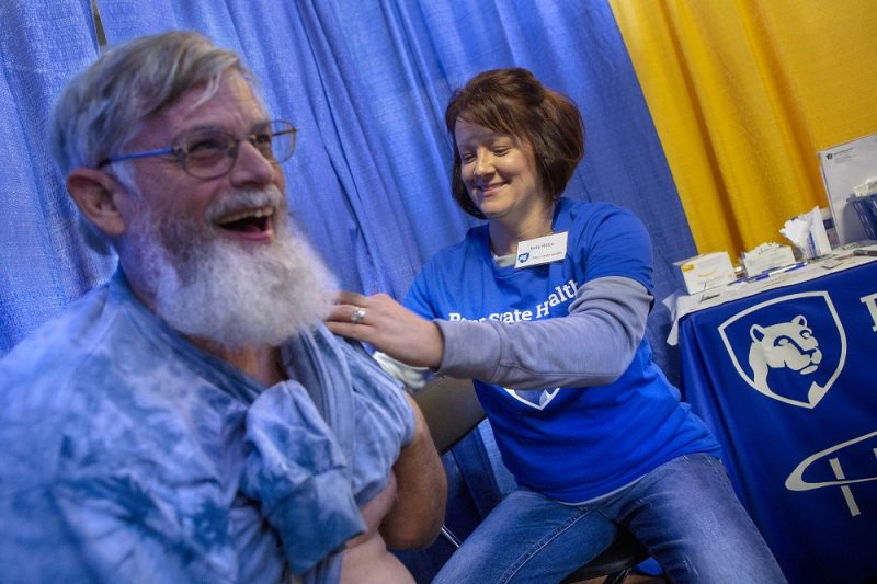 Todd Miller, a man with a long beard and glasses, smiles as a Kelly Rittle, a nurse on his right, holds up his shirt to administer a flu shot, out of the frame. Rittle is flanked by a table upon which is a rendering of the Penn State Nittany Lion in a shield.