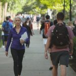 Nina Jablonski is seen walking on an outdoor pathway at Penn State University Park. She is carrying some papers in one arm, walking toward the camera. Other people are seen out of focus, going the other direction.