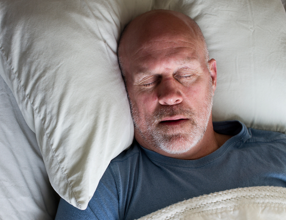 A man lays with his head on a pillow, his eyes closed and his mouth slightly open.