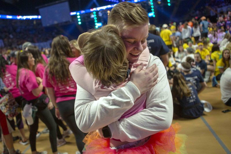 A young man and a child embrace on the floor of THON at the Bryce Jordan Center. The man, facing the camera, is smiling. Several people are in the background – some standing, some seated, slightly out of focus. A stage is also visible.