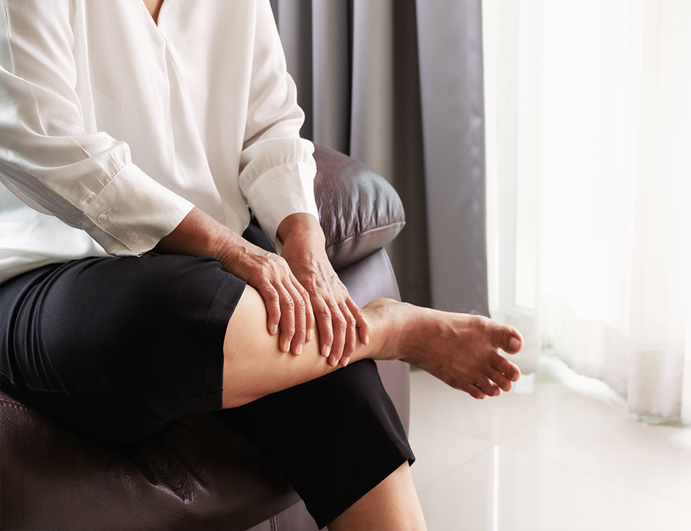 A woman sits on a couch, leaning forward. Her right leg is crossed over her left, and she holds the bottom part of her right leg with both hands.