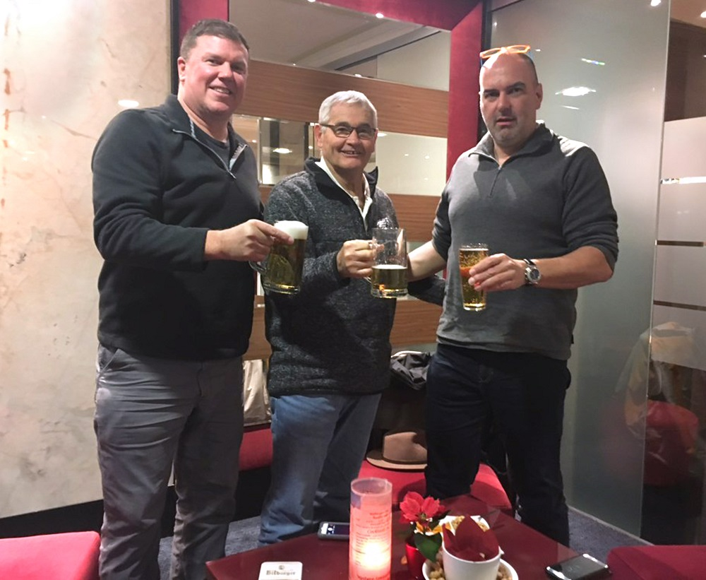 Jim Miller, center, toasts his donor, Stefan Eichert, right, with John Moore, left, the businessman who invited Miller to accompany him on a trip to Germany. All three men are wearing casual shirts and jeans and holding mugs of beer. A candle is on the table in front of them. Behind them is a marbled wall and a wall decorated with slats of wood.
