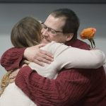 Ashley Brewer receives a hug from organ recipient Bill Griffis at the Rose Parade Donor Remembrance Ceremony. Ashley is a young woman with long hair wearing a sweater and holding a rose. Bill is smiling and has his eyes closed. He is a middle-aged man wearing glasses and a sweater.