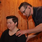 Dr. Peter Seidenberg examines a young woman athlete during the Special Olympics Pennsylvania Winter Games Feb. 10-12. He has a stethoscope in his ears and is holding the diaphragm to her back. He has short hair and is wearing a polo shirt, khaki pants and glasses. The woman is wearing a long-sleeved top and has short hair. Her eyes are closed. Behind them is wood paneling on the wall.