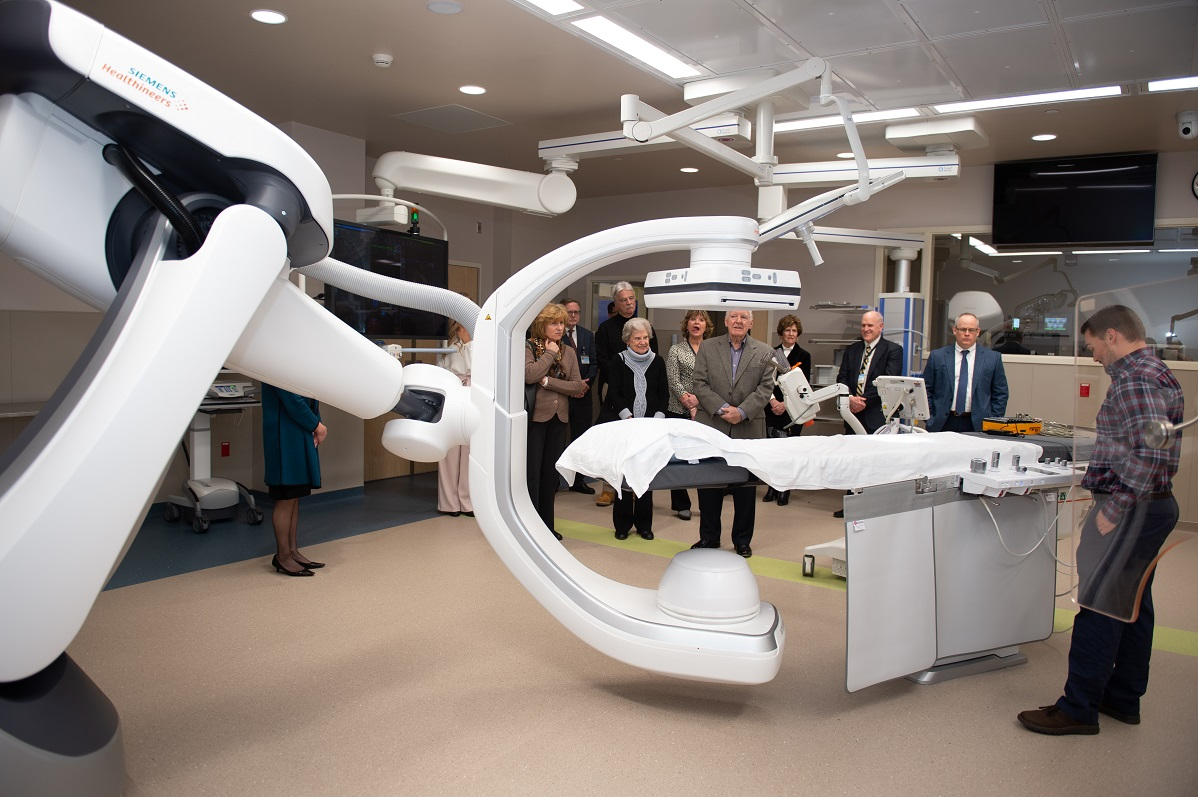 A group of people look at a large piece of medical equipment