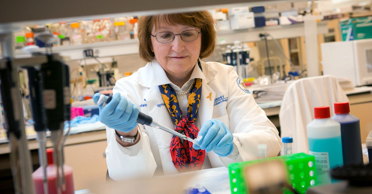 A woman uses a pipetting tool to dispense liquid into a small container, which she holds in her left hand. Various lab equipment is in the background.