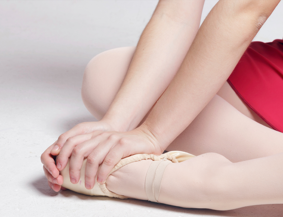 Close-up of a female foot in a ballet slipper, with two hands placed on it.