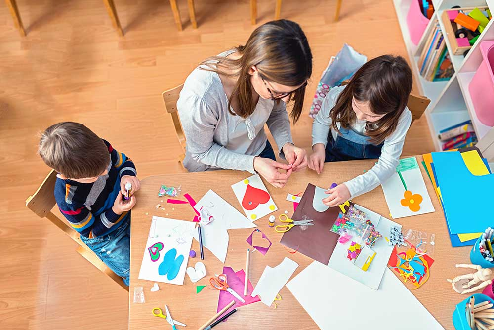 A woman sits between two children at a table, holding something between her fingers. The table is covered with construction paper, scissors, pens and other craft tools.