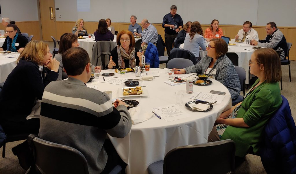 This photo taken Feb. 7, 2019, features a group of Graduate Medical Education program directors and coordinators sitting at round tables eating a meal discussing the wellness topic of the evening and recording ideas to share.